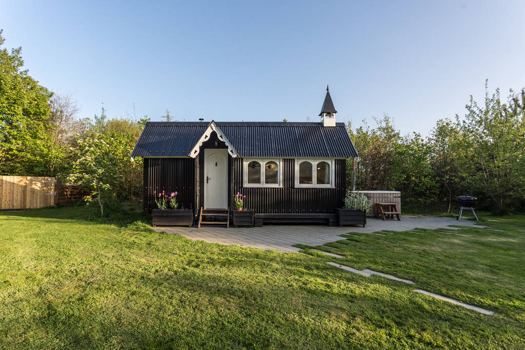 black-st-agnes-tabernacle-with-hot-tub-on-patio-in-field