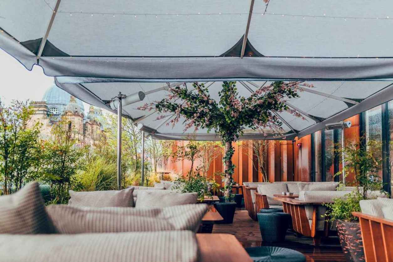comfy-seats-and-tables-on-restaurant-rooftop-overlooking-city-issho