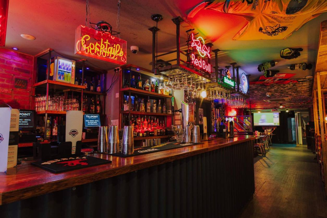 dimly-lit-bar-with-neon-lights-firepit-rocks