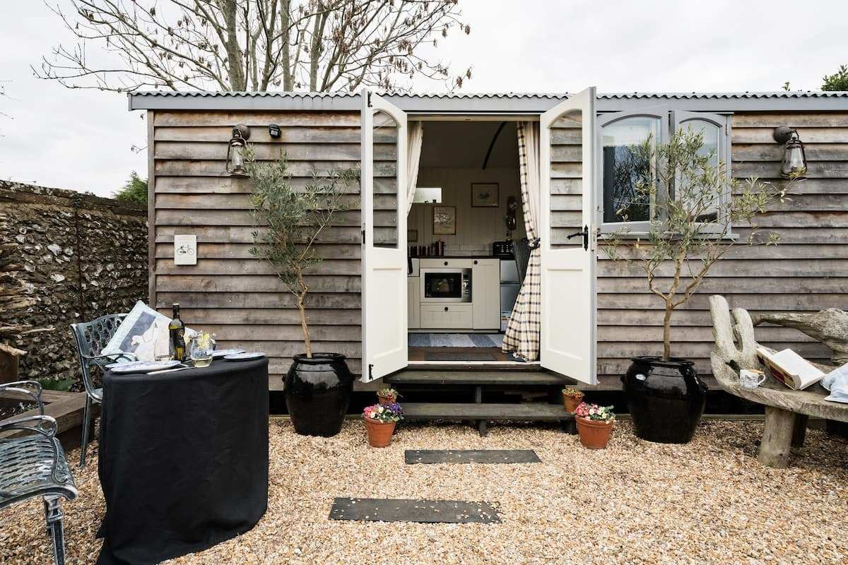 exterior-of-shepherds-hut-with-doors-open-and-outdoor-seating