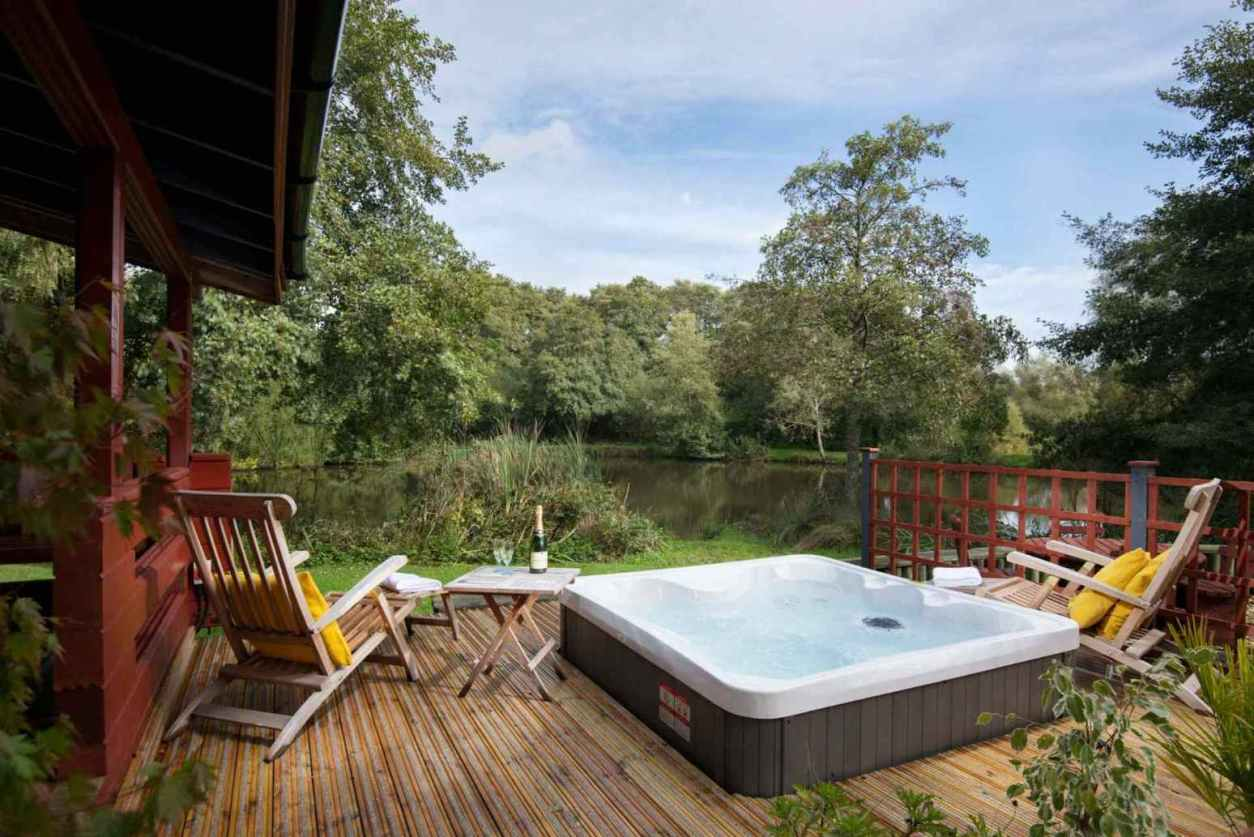 hot-tub-in-decking-of-otter-falls-lodge-overlooking-lake-lodges-with-hot-tubs-devon