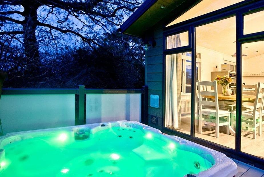 hot-tub-on-decking-of-coleridge-premier-lodge-at-hawkchurch-resort-in-the-evening