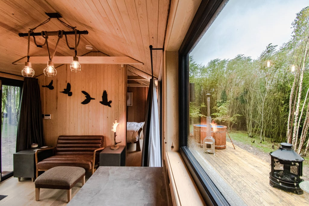inside-coddiwomple-cabin-on-decking-with-hot-tub-outside-at-downash-wood-glamping-sussex
