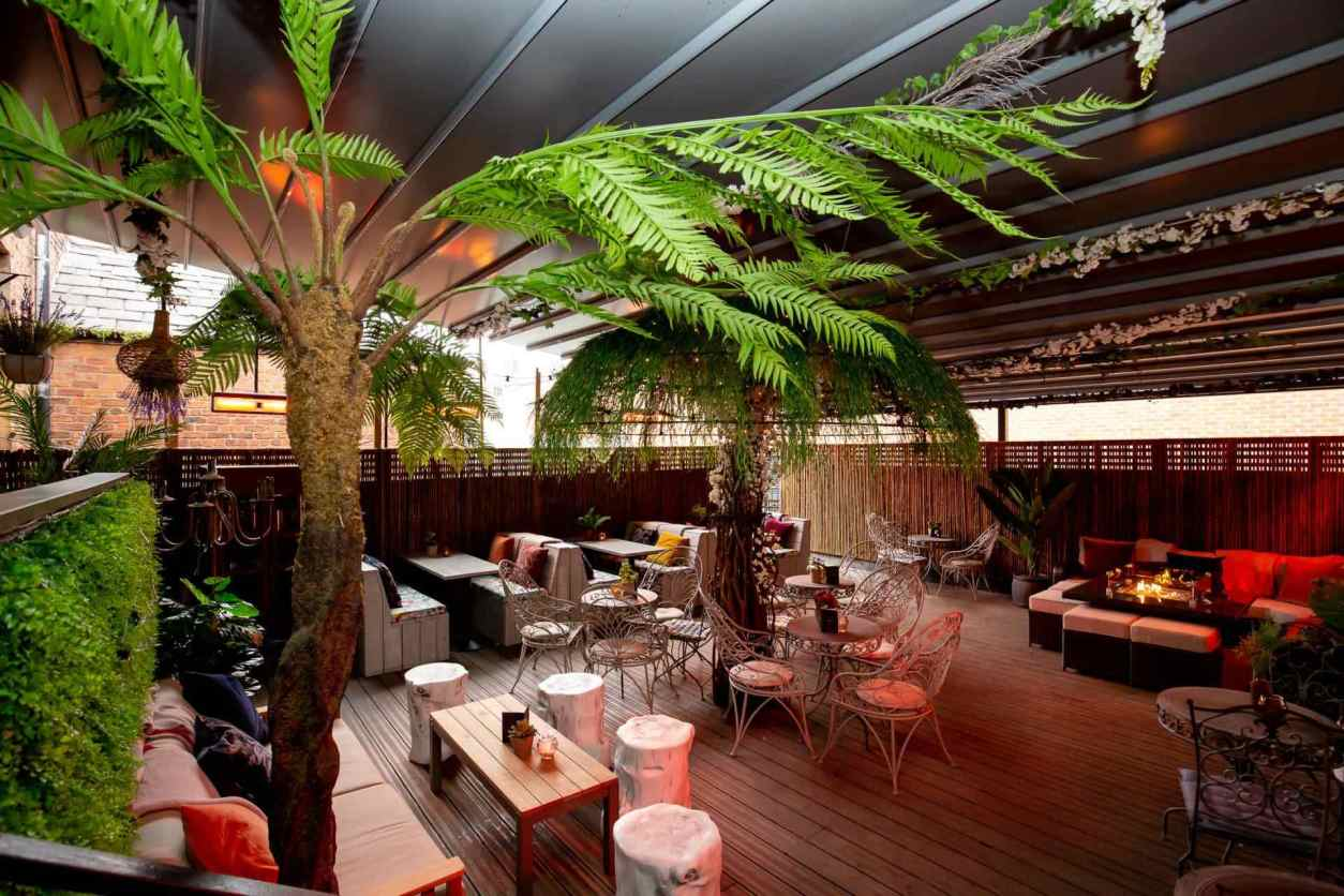 outdoor-space-with-fake-palm-trees-at-red-door-bar-best-cocktail-bars-liverpool