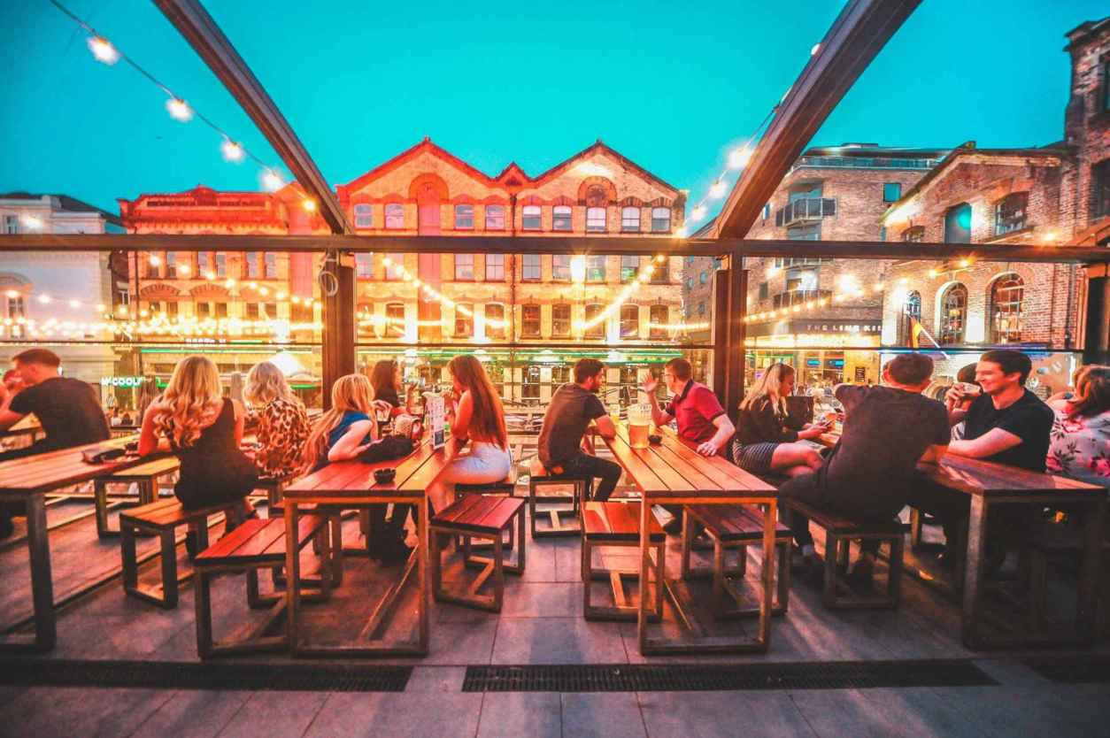 people-sat-drinking-on-rooftop-of-modo-bar-in-evening-best-cocktail-bars-liverpool