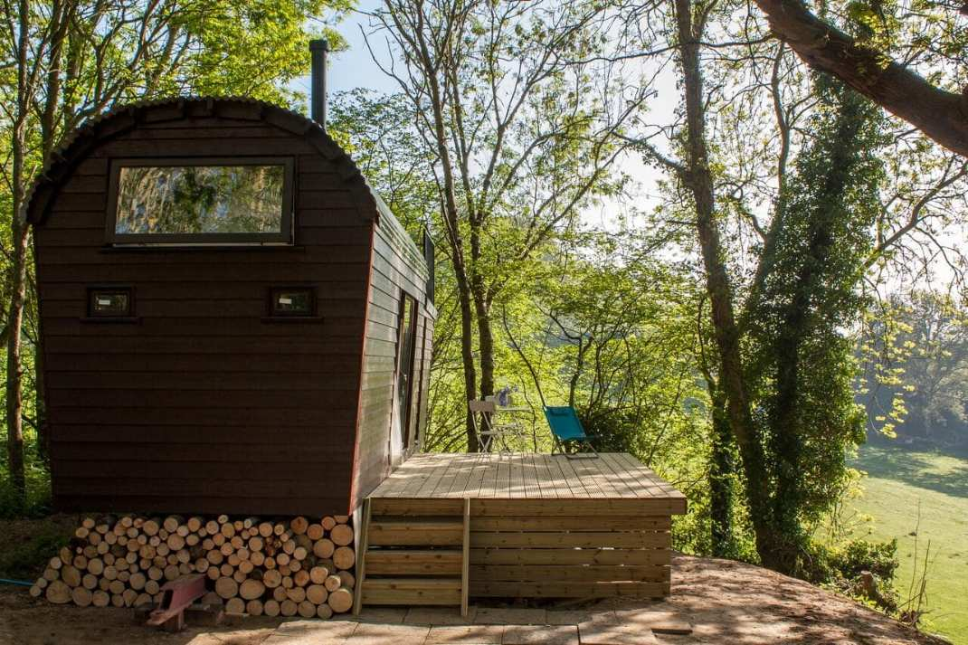 tall-black-the-hide-out-cabin-on-decking-in-forest