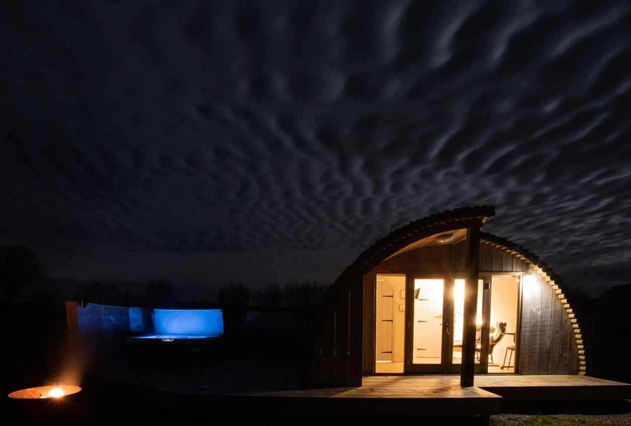 three-moors-view-log-cabin-with-hot-tub-lit-up-at-night-lodges-with-hot-tubs-devon
