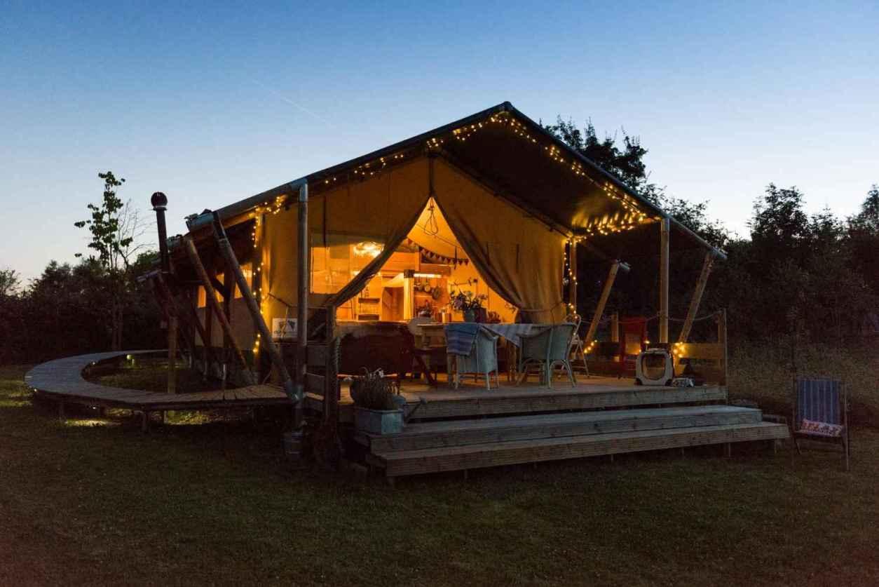 up-sticks-glamping-safari-tent-lit-up-at-night