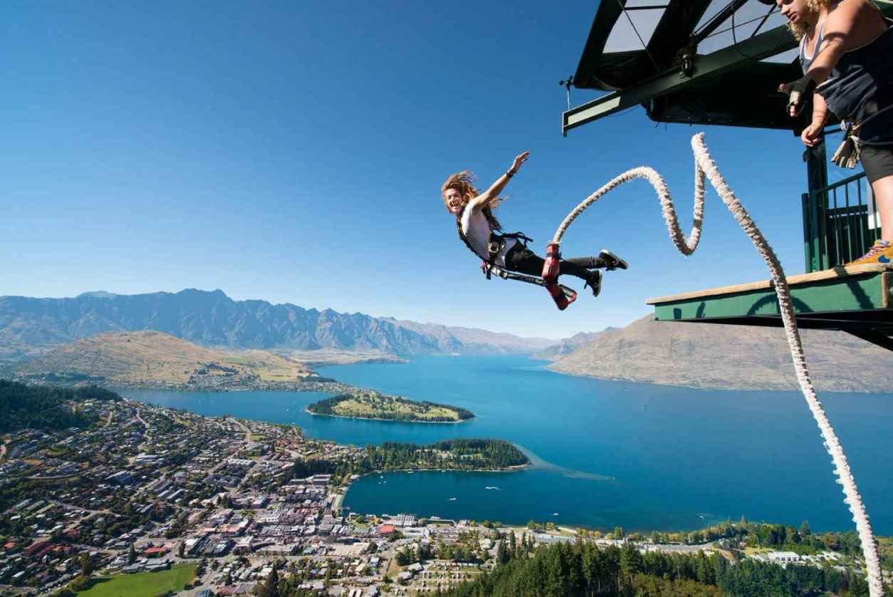 woman-bungee-jumping-from-aj-hackett-ledge-with-lake-in-background