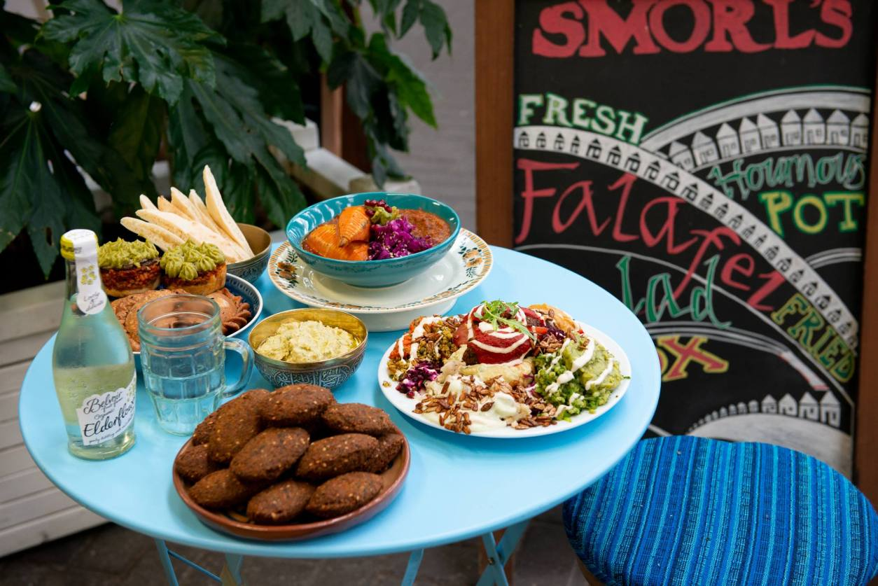 plates-and-bowls-of-food-on-round-blue-table-at-smorls-best-vegan-restaurants-brighton