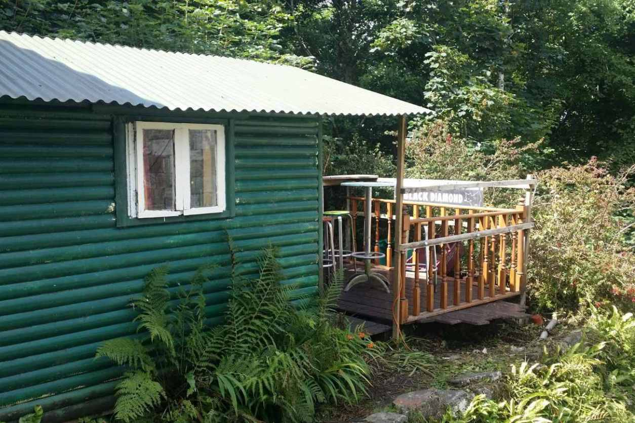 teal-waterfall-hut-with-decking-in-forest