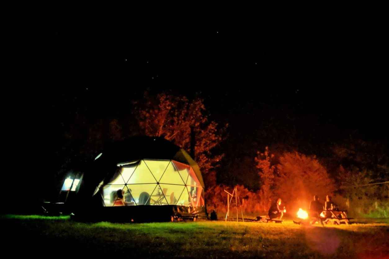 top-of-the-woods-nature-dome-lit-up-at-night-by-campfire