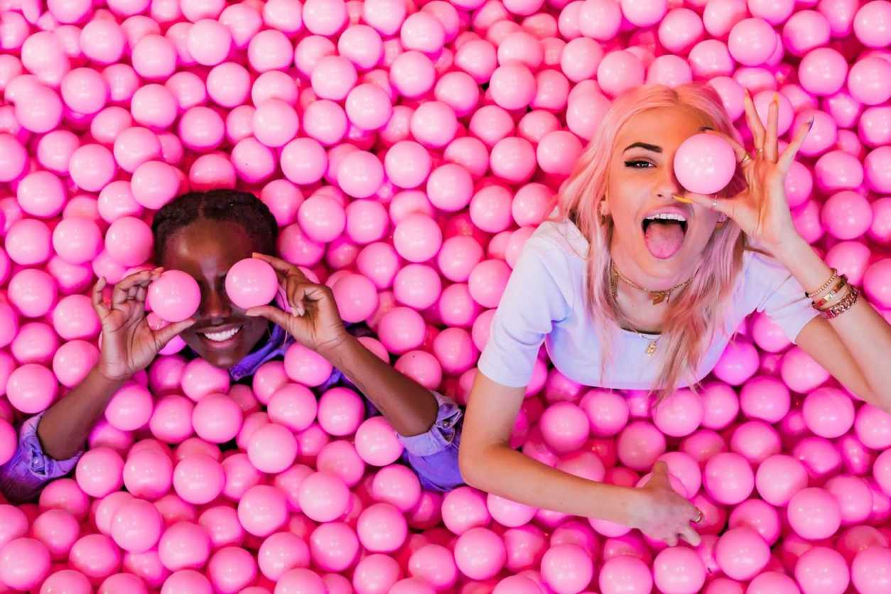 two-young-women-in-pink-ball-pit-at-ballie-ballerson