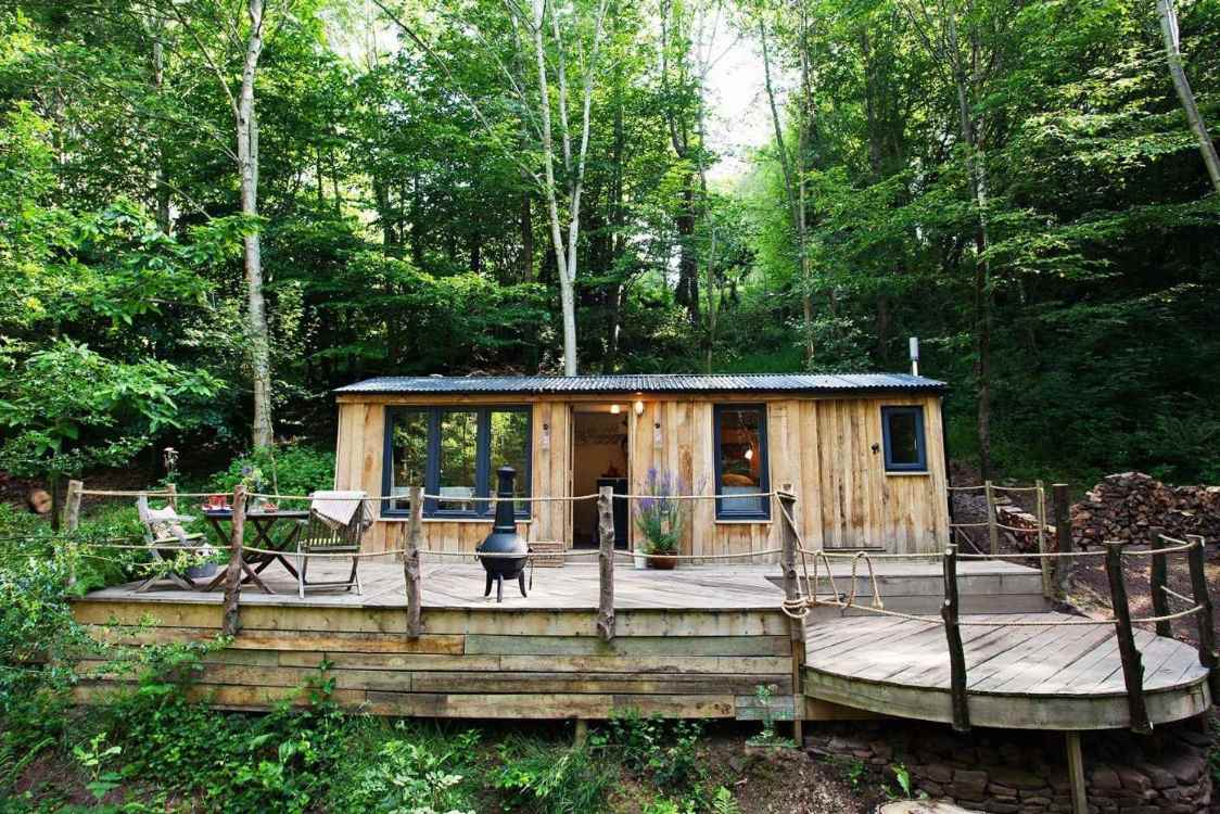 wood-shack-cabin-with-large-decking-in-woodland