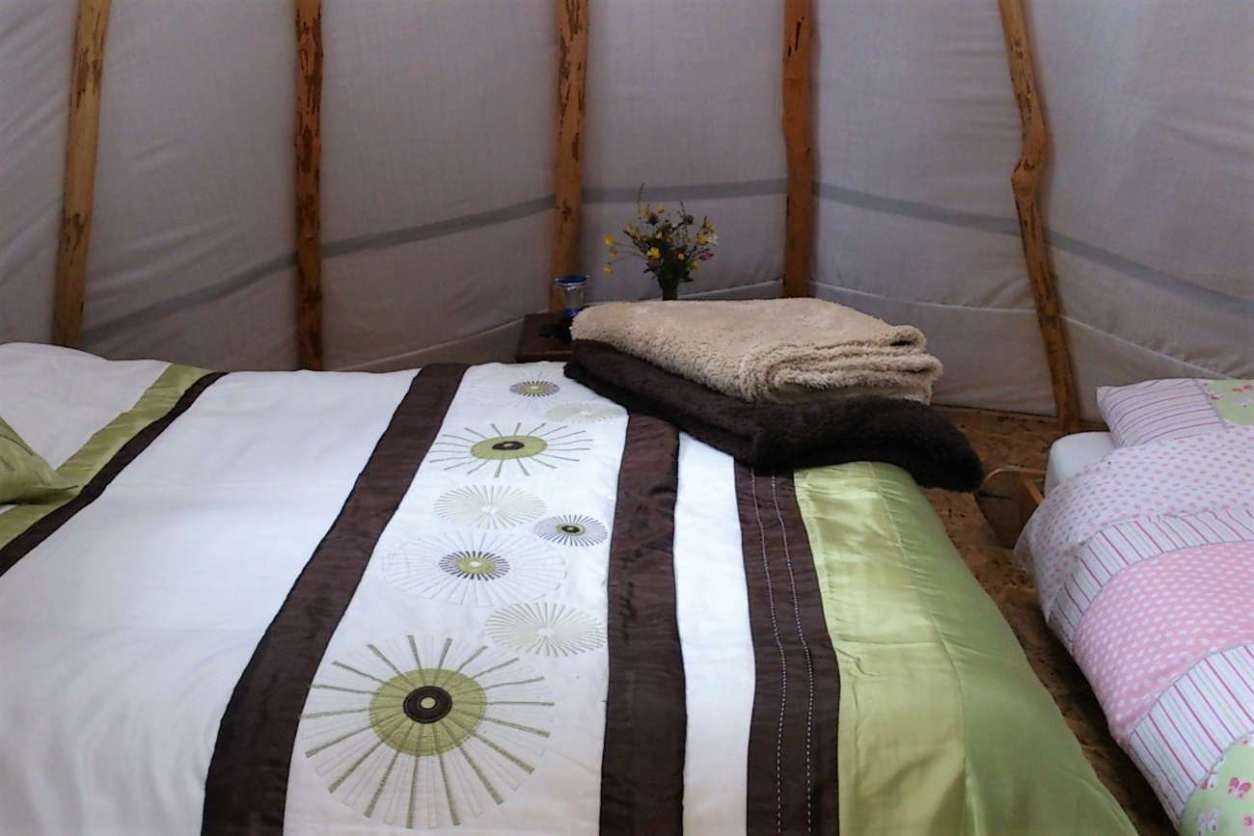 beds-and-towels-inside-pink-apple-orchard-tipi