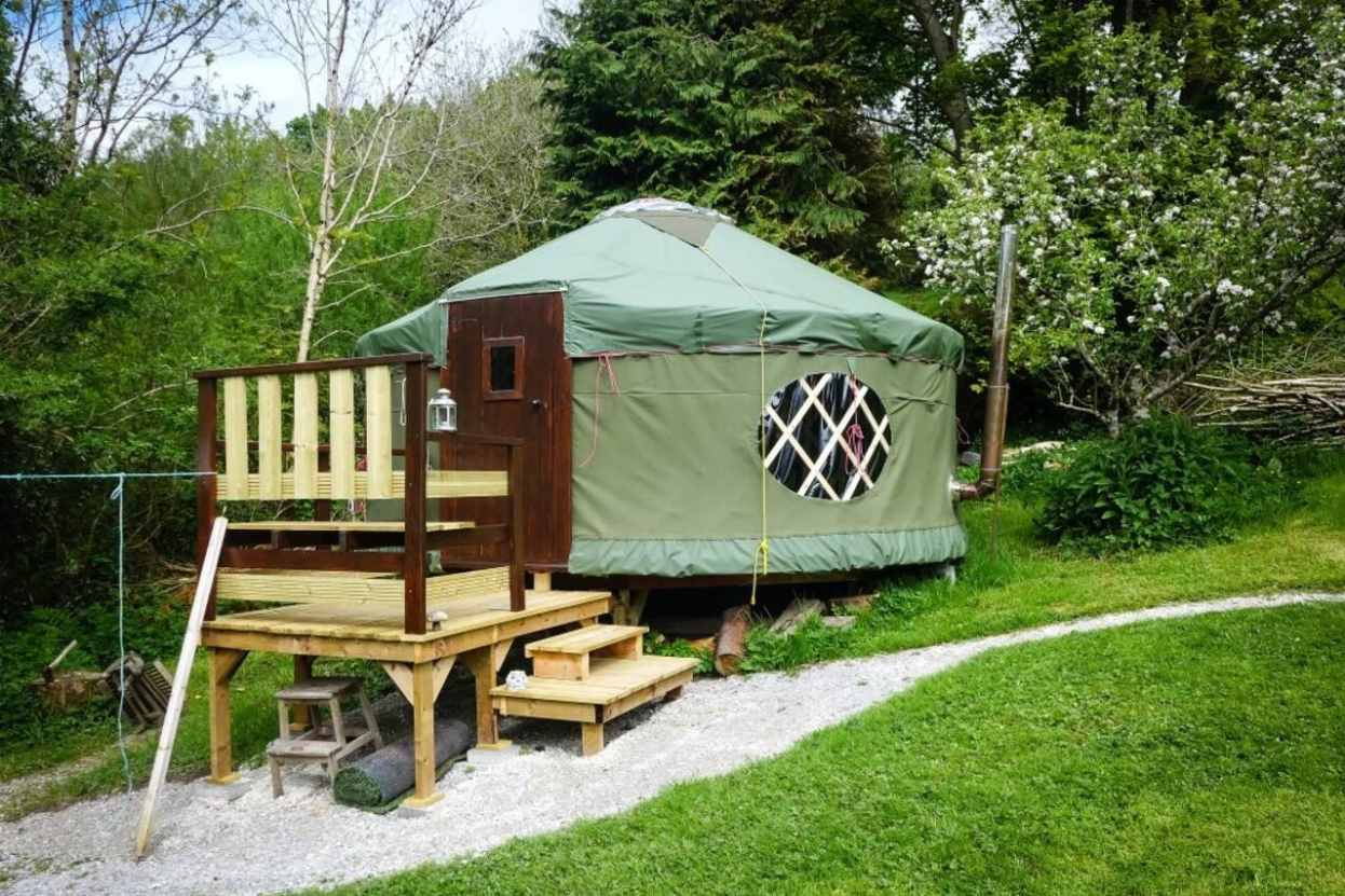 green-bigfoot-yurt-with-decking-by-trees