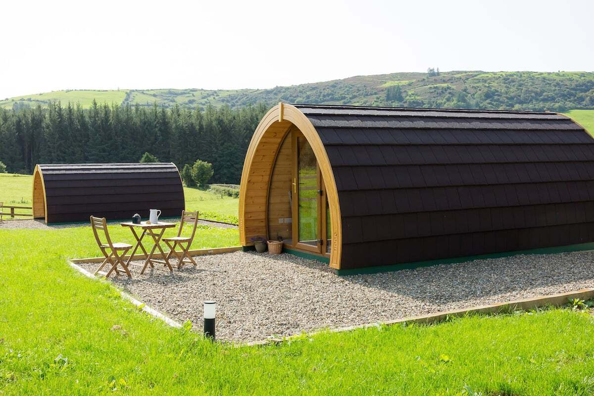 two-kilbane-glamping-pods-in-field-by-forest