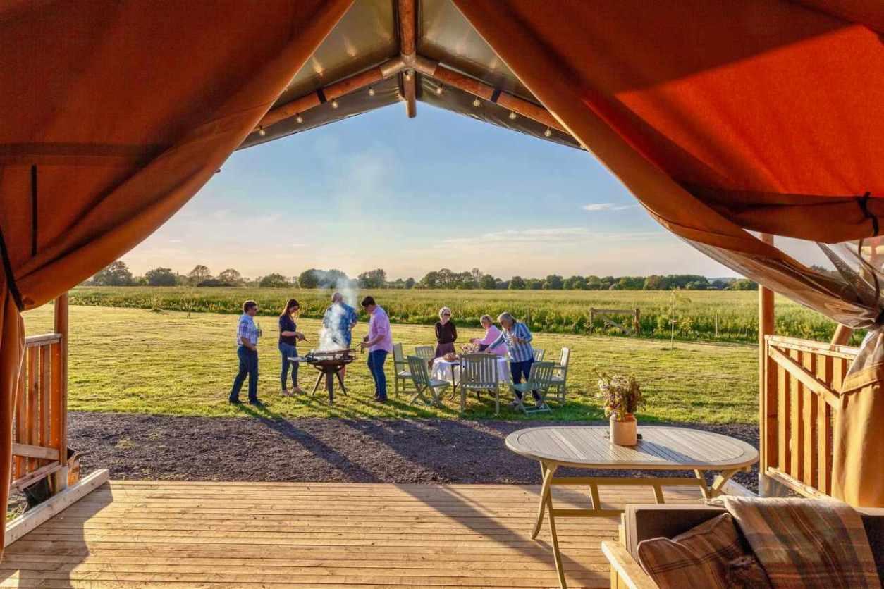 adults-having-a-bbq-outside-gravel-pit-farm-safari-tent