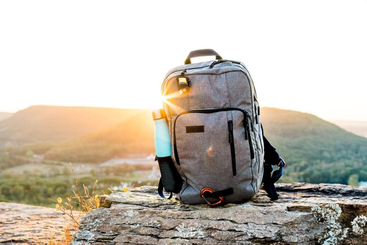 backpack-and-water-bottle-on-rock-on-mountain-road-trip-packing-list