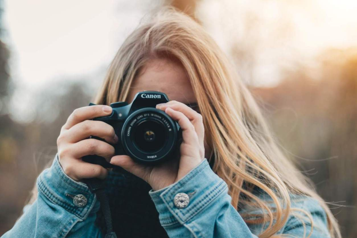 blonde-girl-taking-photo-with-canon-dslr-camera-road-trip-packing-list