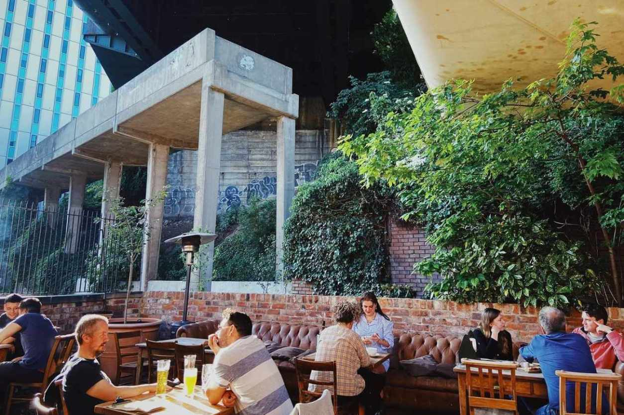people-drinking-under-bridge-at-the-bridge-tavern-pub
