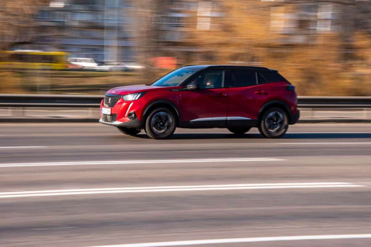 red-peugeot-2008-suv-driving-down-road-trip-packing-tips