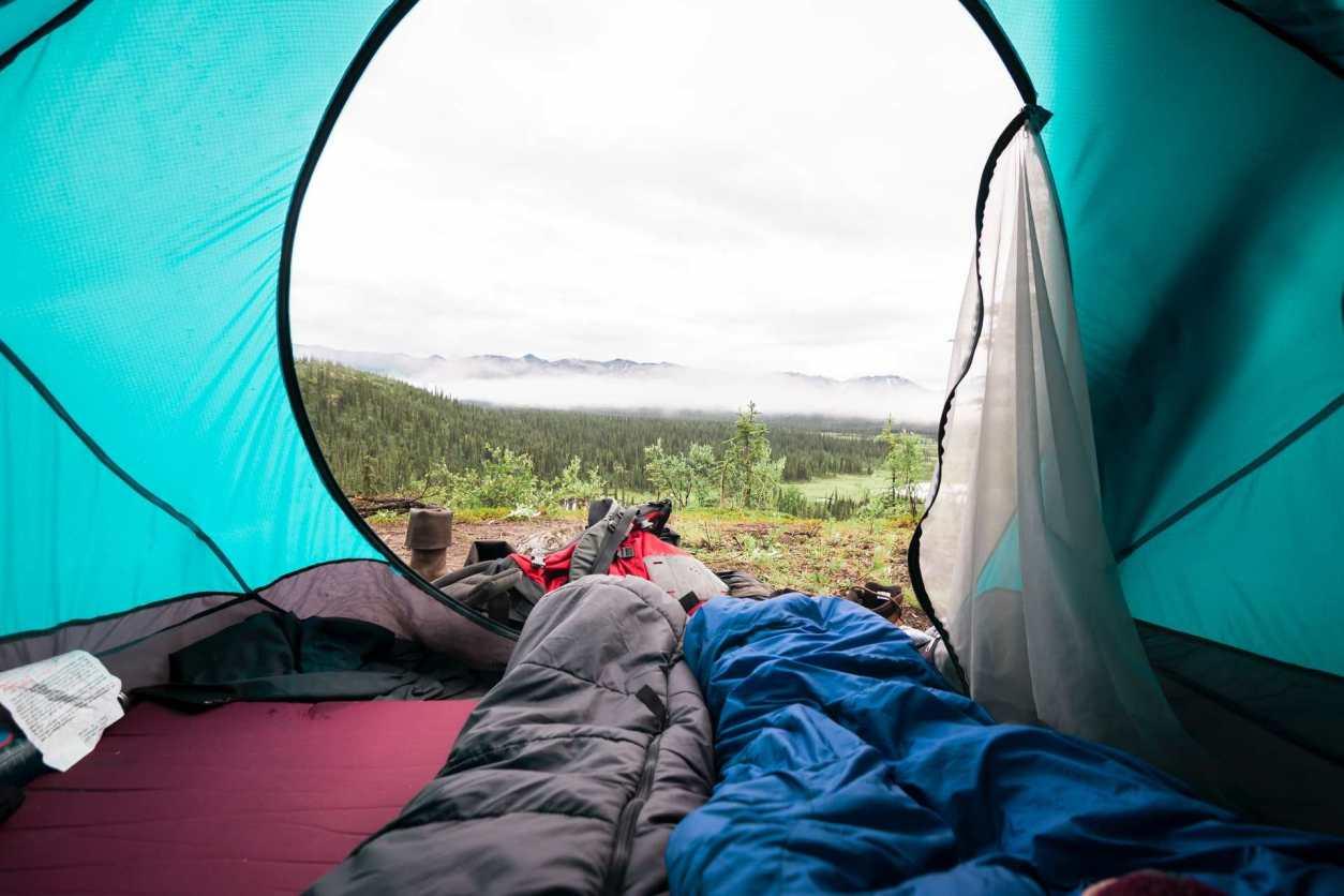 sleeping-bags-in-tent-overlooking-view-road-trip-packing-list