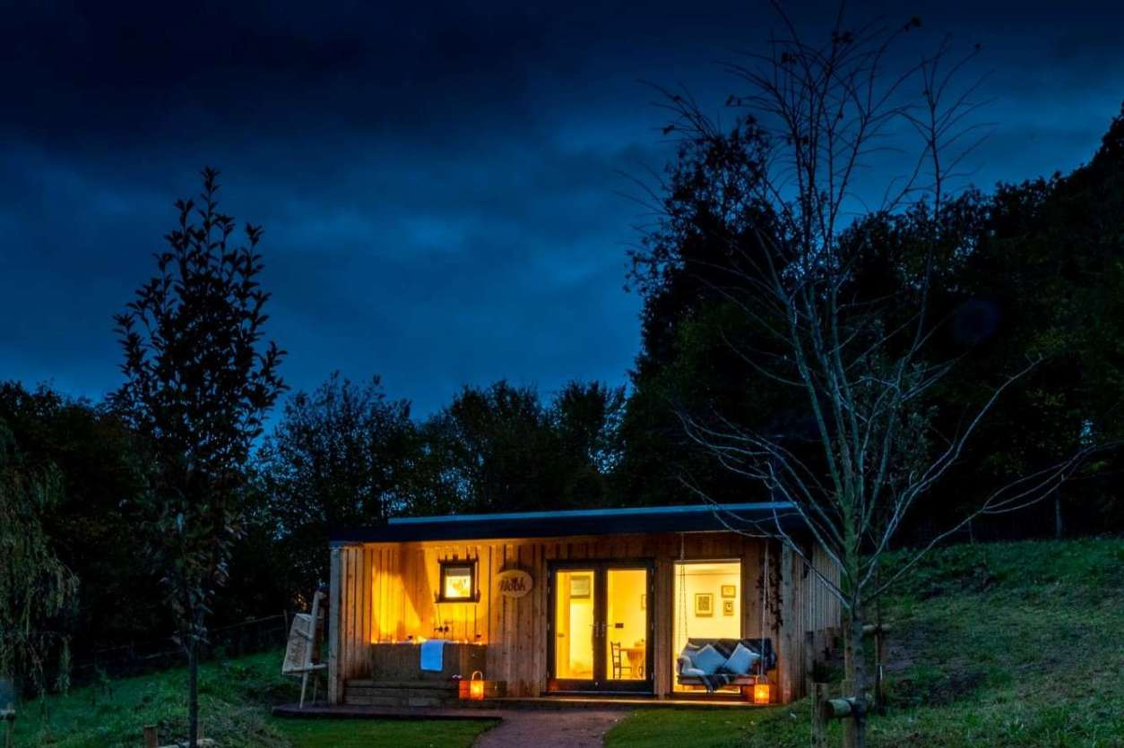 the-nook-cabin-at-the-roost-glamping-lit-up-at-night-glamping-gloucestershire