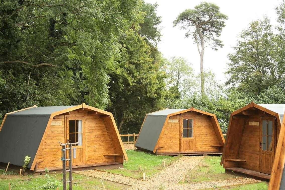 three-the-wildings-glamping-pods-in-field