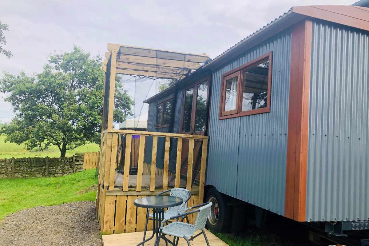 exterior-of-blue-luxury-shepherds-hut-with-outdoor-seating