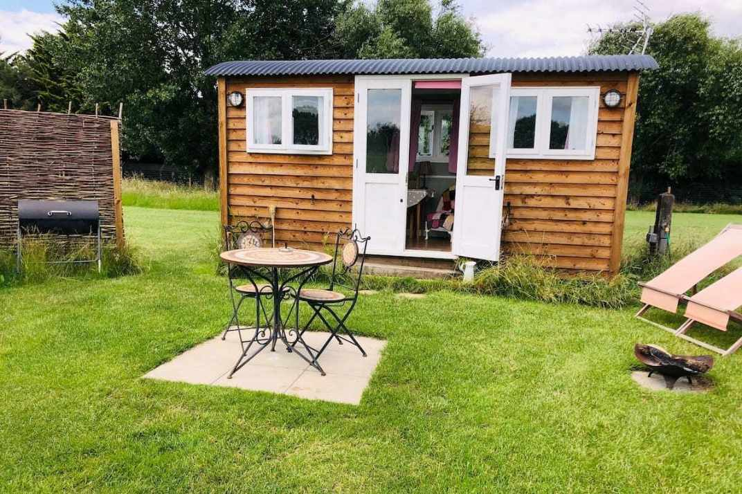exterior-of-lazy-goose-shepherds-hut-in-field-in-daytime