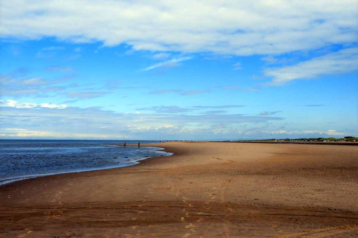 people-walking-down-ainsdale-sands-beach-on-sunny-day
