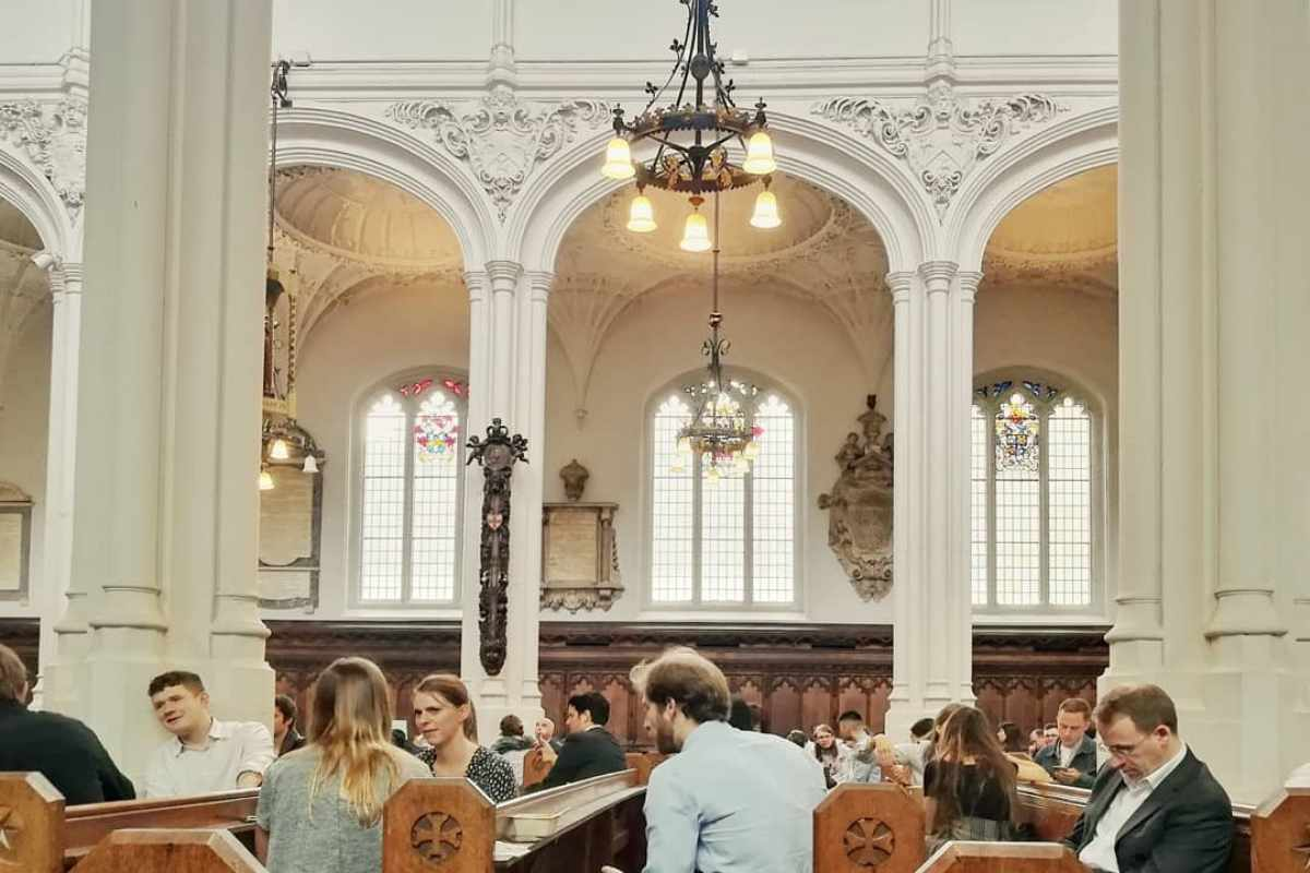 people-sitting-on-church-pews-in-host-cafe