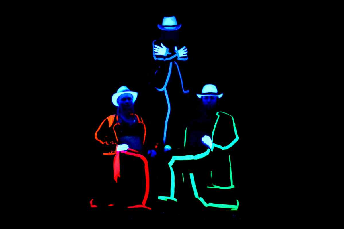 three-people-lit-up-in-darkness-at-black-light-theatre