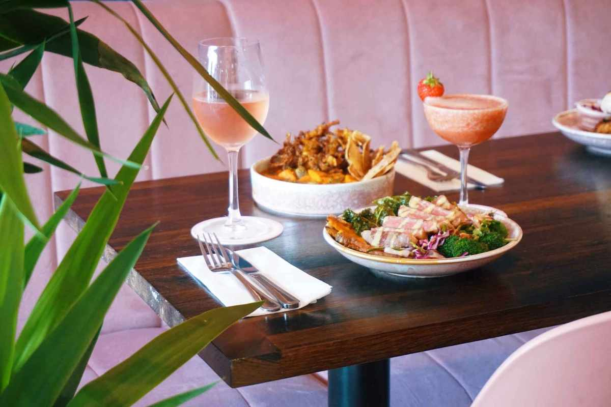 two-plates-of-food-a-cocktail-and-glass-of-wine-on-table-at-east-river