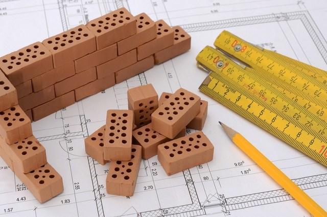 Il simbolo dell'impresa edile: metro da cantiere, matita, progetto e mattoncini