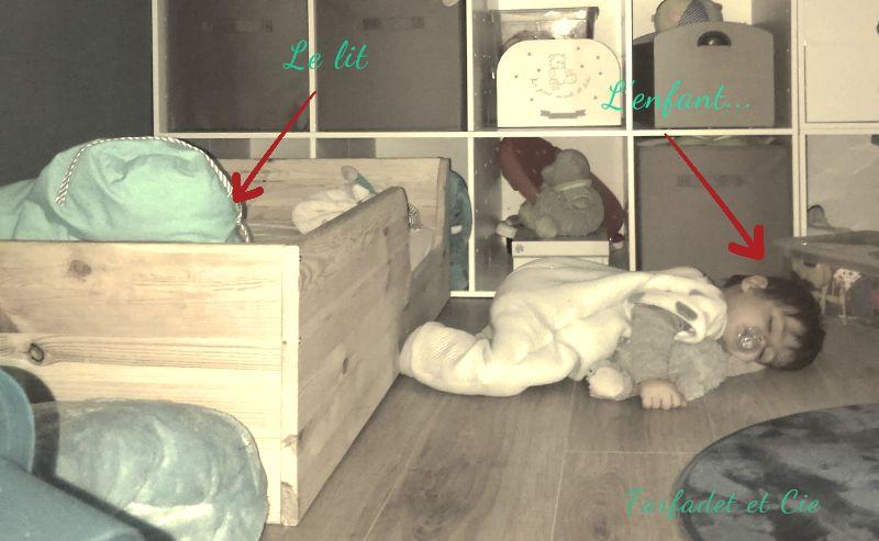 bébé dort à côté du lit au sol