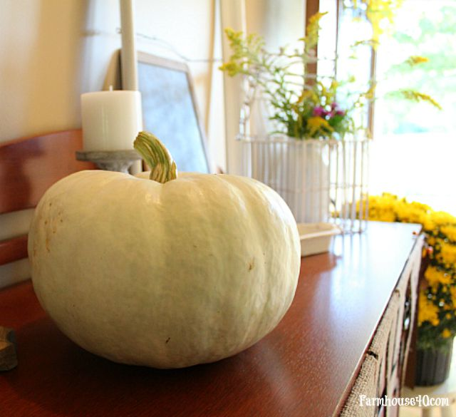 fall entry white pumpkin candle and wildflowers in mason jar