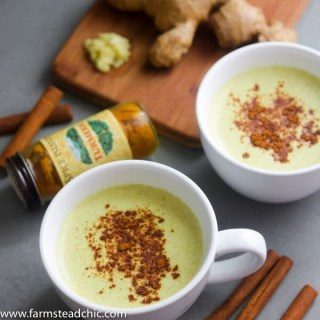 Two Paleo and Whole30 Ginger Turmeric Lattes with cinnamon sticks, fresh ginger and a bottle of ground turmeric.