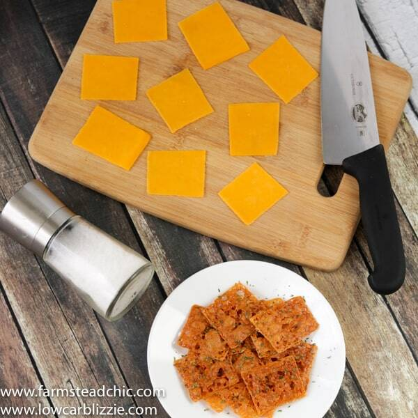 keto crackers with a cutting board and knife, slices of fresh cheese and a salt grinder