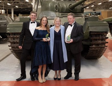 The Hannam Family stand in front of a tank at the Dorset Tourism Awards 2019 after Farmstead glamping won Gold and Silver Awards