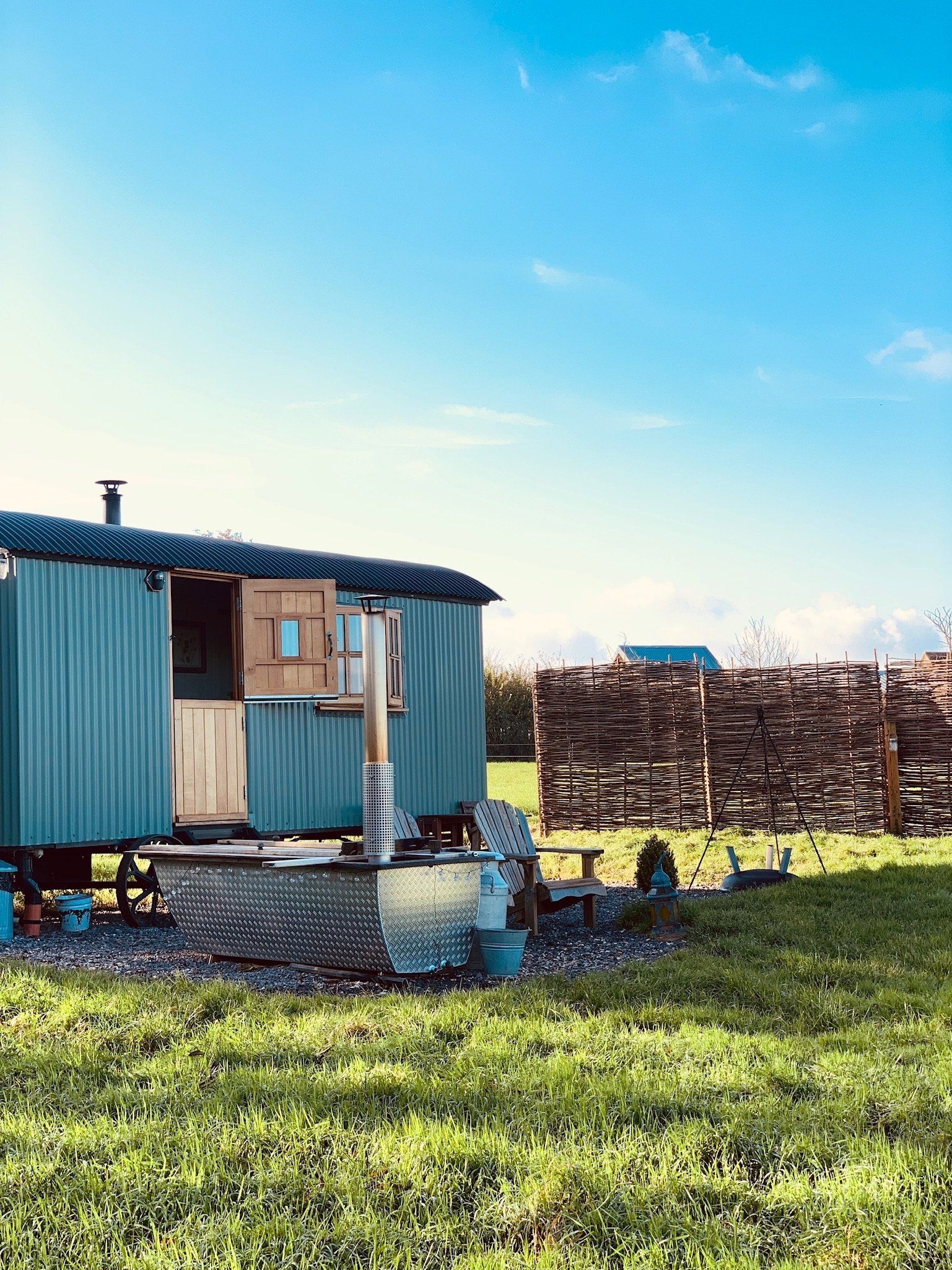 Clear blue skys above a green shepherd hut with a Hikki Bohemen wood buring hot tub outside