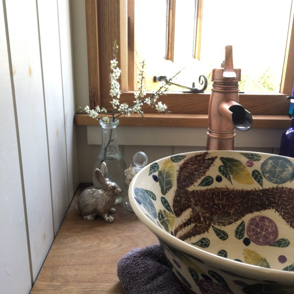 A beautiful hand thrown sink by Jo Burnell decorated with Hares and leaves sits in a small oak window on a sunny spring day
