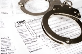 Stock image of handcuffs over Tax forms, concepts: Tax fraud or Slave to the Taxes