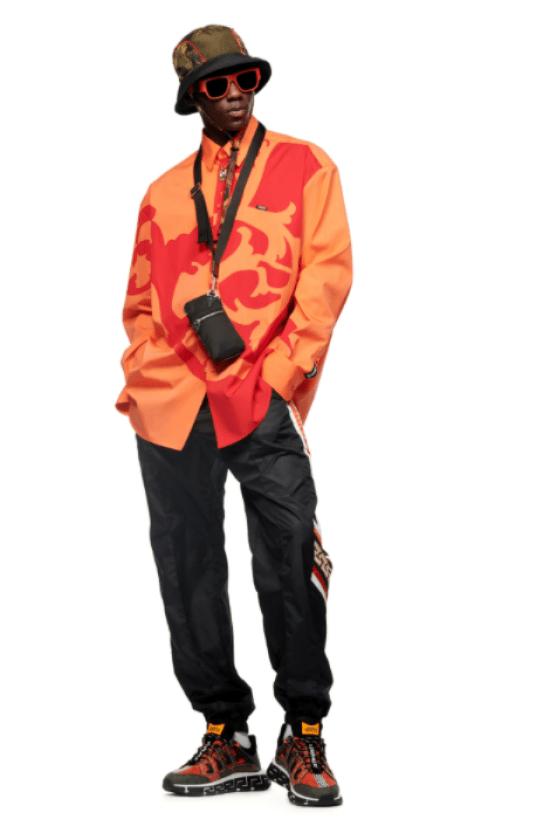 Bolsa masculina pendurada no pescoço, camisa laranja e calça sportswear masculina
