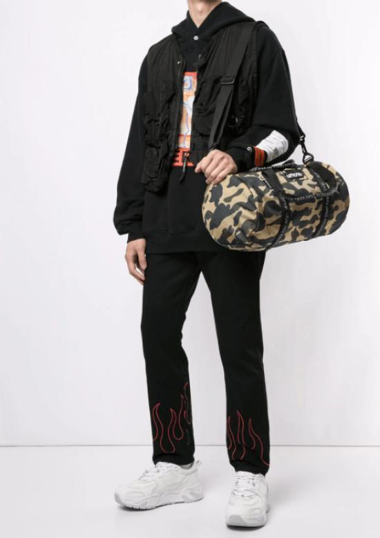 Bolsa de ginástica cilíndrica camuflada com moletom, colete e calça reta.