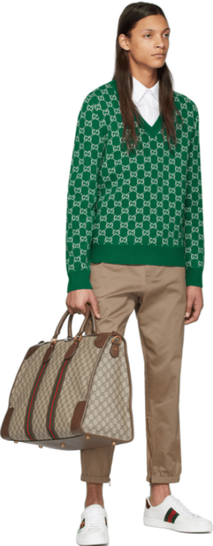 Bolsa de mão Gucci, tricô sobreposto à camisa branca e calça bege e tênis Gucci