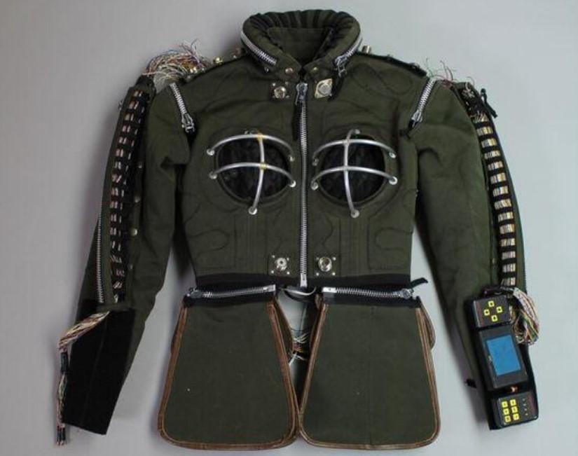 Foto de uma jaqueta verde com diversos tipos de zíper e outros adornos, como um aparelho eletrônico e armações de metal