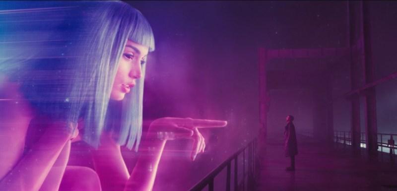 Cena de Blade Runner 2049 com uma mulher virtual tentando tocar um humano.
