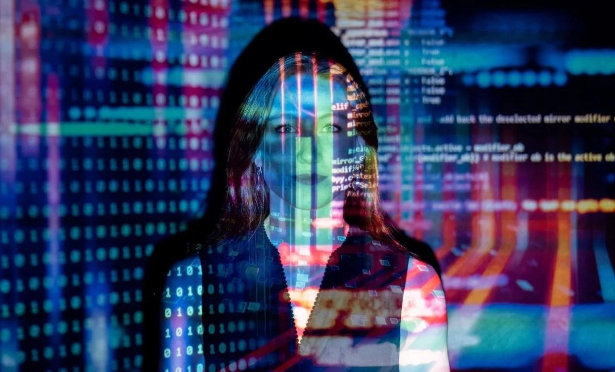 Foto de uma mulher com projeção de códigos informáticos.